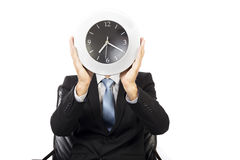 Closeup of businessman covering his face with a wall clock Royalty Free Stock Photos
