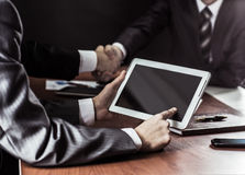 Closeup of businessman with digital tablet in the background of handshake of business partners. Royalty Free Stock Images