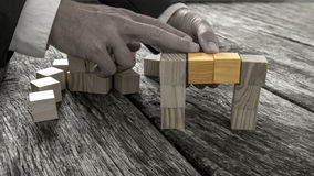 Closeup of businessman forming a bridge of small wooden blocks i Stock Images