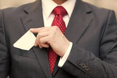 Closeup of Businessman hand holding a business card over suit pocket Isolated on white. Businessman in suit and red tie drawing royalty free stock photography