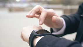 Closeup of businessman hand using his smartwatch touchscreen standing on the street. Closeup of businessman using his smartwatch touchscreen standing on street stock video
