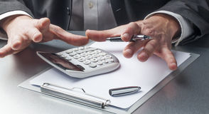 Closeup on businessman hands displaying calculator and notes for financial concept Royalty Free Stock Photography