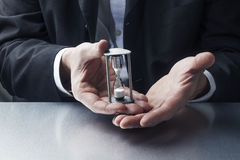 Closeup on businessman hands displaying hourglass or egg timer for time concept Royalty Free Stock Images