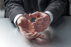 Closeup on businessman hands with handcuffs on for concept of crime or justice at work Royalty Free Stock Images