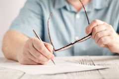 Closeup of businessman hands writing something on piece of paper and holding pair of glasses Stock Photo