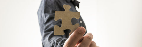 Closeup of businessman holding a blank puzzle piece towards you Stock Image