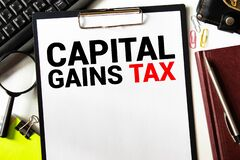 Closeup on businessman holding a card with text CAPITAL GAINS TAX