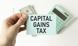 businessman holding a card with text CAPITAL GAINS TAX, business concept image with soft focus background and vintage