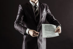 Closeup of a businessman holding a pen and a document with the terms of the contract. Businessman holding a pen and a document with the terms of the contract Royalty Free Stock Photo