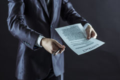 Closeup of a businessman holding a pen and a document with the terms of the contract. Businessman holding a pen and a document with the terms of the contract Royalty Free Stock Images