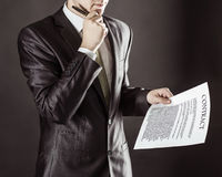 Closeup of a businessman holding a pen and a document with the terms of the contract. Businessman holding a pen and a document with the terms of the contract Stock Photography