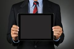 Businesman Holding Blank Tablet Computer. Closeup of a businessman holding Tablet Computer with a blank screen in front of his torso. Horizontal format over a Stock Photos