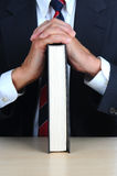 Closeup of a businessman leaning on book at desk royalty free stock photography