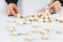 Closeup of businessman making a pyramid with empty wooden cubes. Concept of business hierarchy stock image