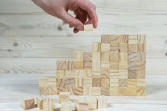 Businessman making a pyramid with empty wooden cubes. Closeup of businessman making a pyramid with empty wooden cubes. Concept of business hierarchy royalty free stock image