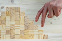 Businessman making a pyramid with empty wooden cubes. Closeup of businessman making a pyramid with empty wooden cubes. Concept of business hierarchy royalty free stock photography