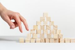 Closeup of businessman making a pyramid with empty wooden cubes. Concept of business hierarchy royalty free stock photos