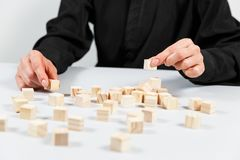 Closeup of businessman making a pyramid with empty wooden cubes. Concept of business hierarchy stock photography