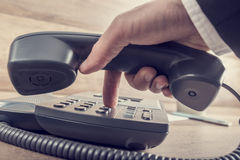 Closeup of businessman making a telephone call by dialing a phon Royalty Free Stock Images
