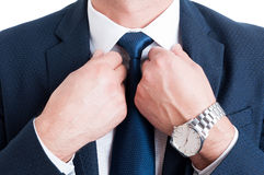 Closeup with businessman necktie fixing white collar. And wearing elegant wrist watch Stock Photo