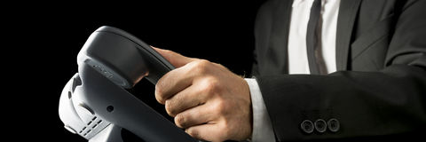 Closeup of businessman picking up  a black landline telephone re Stock Image