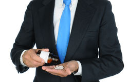 Businessman Pouring Pills into His Hand Royalty Free Stock Photography
