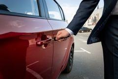 Closeup of businessman pulling car door handle Stock Photo