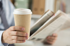 Closeup of businessman reading news and holding coffee cup. Closeup view of businessman hand holding cardboard coffee cup and reading morning newspaper royalty free stock images