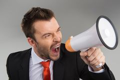 Closeup of businessman screaming in megaphone  on grey background. Royalty Free Stock Photography
