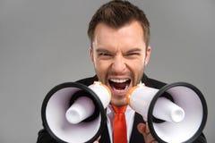 Closeup of businessman screaming in two megaphones  on grey background. Businessman speaking loud through megaphones Royalty Free Stock Photo