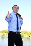 Closeup of businessman showing ok. With focus on a hand at nature background stock photography