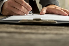 Closeup of businessman signing contract, document or legal paper. S clipped on clipboard with fountain pen Stock Image