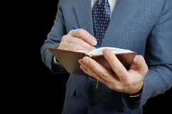 Closeup of a businessman taking notes in a small notebook. Royalty Free Stock Images