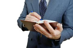 Closeup of a businessman taking notes in a small notebook. Royalty Free Stock Photo