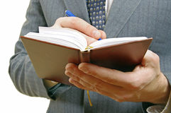 Closeup of a businessman taking notes in a small notebook. Stock Photography