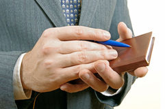 Closeup of a businessman taking notes in a small notebook. Stock Photos