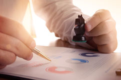 Closeup of businessman working with document graph and holding a chess piece. Royalty Free Stock Photography