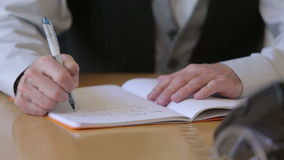 Closeup of a businessman writing in a note pad stock video