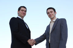Closeup of businessmen shaking hands over a deal. On sky background royalty free stock photography
