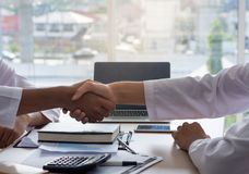 Businessmen shaking hands over deal negotiation to success with laptop at office. Closeup of a businessmen shaking hands over deal negotiation to success with Royalty Free Stock Image