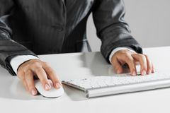 Closeup of businesswoman hand typing on keyboard with mouse on wood table royalty free stock photography
