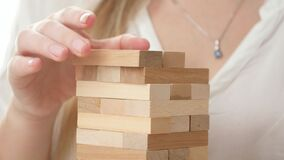 Closeup of businesswoman putting blocks and bricks of high tower. Concept of stability, development, success and