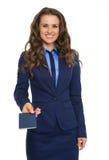 Closeup of businesswoman in suit handing over blue passport Stock Photos