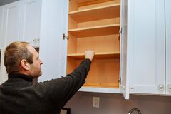 Closeup of a cabinet installer installing hardware on new kitchen cabinets. Installing new kitchen royalty free stock photo