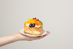 Closeup of cake with fresh fruits on gray background. Stock Image