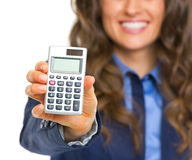 Closeup on calculator in hand of smiling business woman Stock Photography