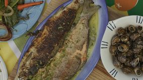 Closeup, camera pan of fried Salmo ohridanus. Belvica, Ohrid trout, snails and vegetables stock video