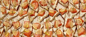 Closeup of canapes with cream cheese, salmon, greens and lemon stock photo
