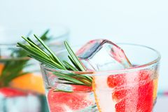 Closeup of a cape cod cocktail or vodka cranberry on a blue background. The closeup of a cape cod cocktail or vodka with fruits on blue studio background Royalty Free Stock Image