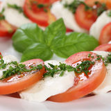 Closeup Caprese salad with tomatoes and mozzarella cheese on pla Royalty Free Stock Image